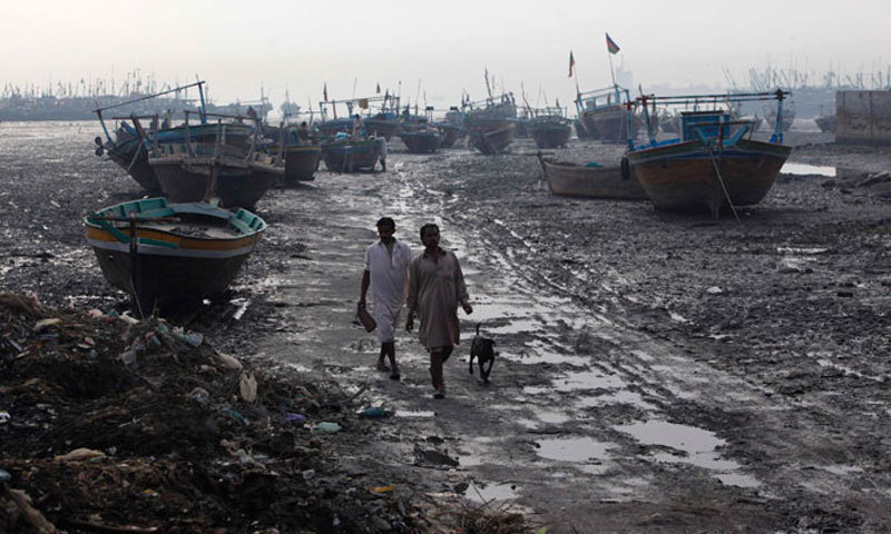 Fishermen walk past an area of Ibrahim Hyderi. — Photo by Reuters