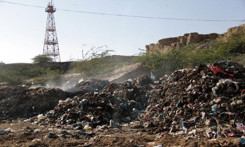 Mounds of rubbish burn near reclaimed road in Ibrahim Hyderi. — Photo by White Star