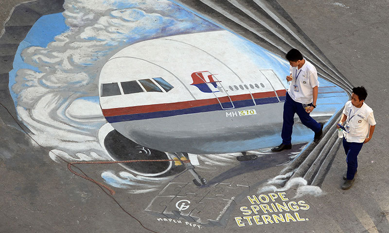 Students walk past a giant mural featuring missing Malaysia Airlines flight MH370 displayed on the grounds of their school in Manila's financial district of Makati on March 18, 2014. – AFP Photo