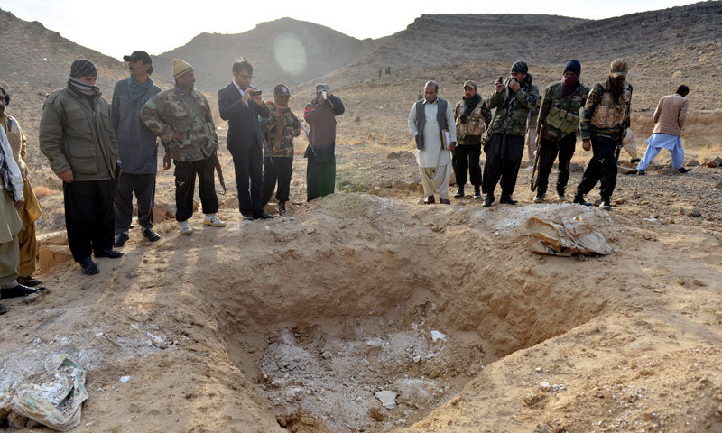 Officials stand near the graves discovered in Tootak. — Photo by Fahim Siddiqui/White Star