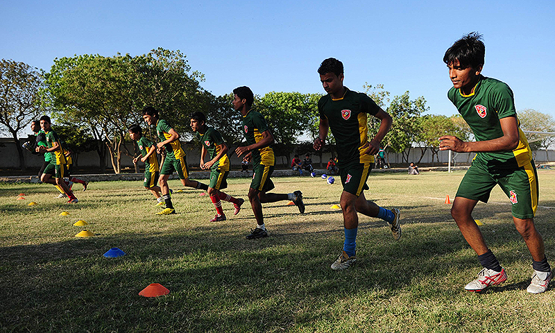 This photograph taken on March 17, 2014, shows Pakistani street children taking part in a football training camp in Karachi. -Photo by AFP