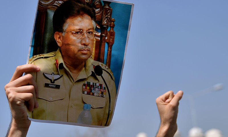 A supporter of former military ruler Pervez Musharraf holds his photograph as he shouts slogans during a protest outside the special court set up to try Musharraf during a hearing in Islamabad, March 31, 2014. Photo by AFP
