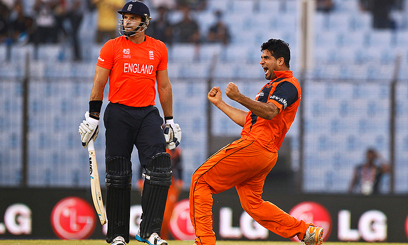 Netherlands's Mudassar Bukhari, right, celebrates the wicket of England's Michael Lumb, left. -Photo by AP