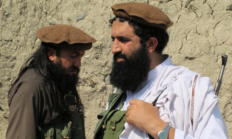 In this Oct 5, 2013 photo, TTP spokesman Shahidullah Shahid, right, arrives for an interview at an undisclosed location in Pakistan's tribal areas. — Photo by AP