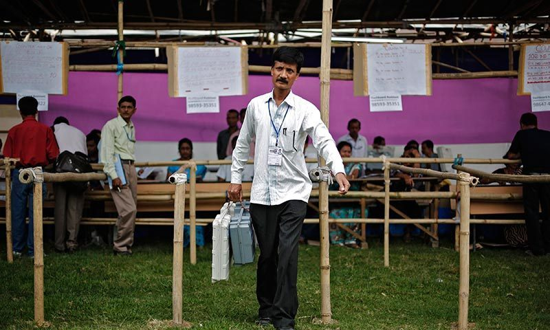 A polling officer carries an electronic voting machine (EVM) after collecting it from a distribution centre ahead of general elections in Jorhat district, in the northeastern Indian state of Assam. —Photo by Reuters