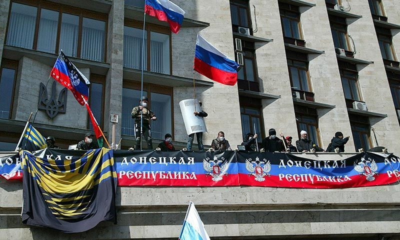 """Activists wave Russian national flags on the balcony of the regional administration building decorated a banner reading """"Donetsk Republic,"""" in Donetsk, Ukraine. -AP Photo"""