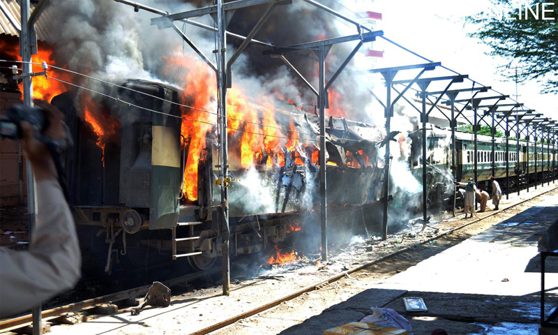 SIBI: Smoke and flames rise from a carriage after an explosion in Jaffar Express at the railway station, here on Tuesday.—Online