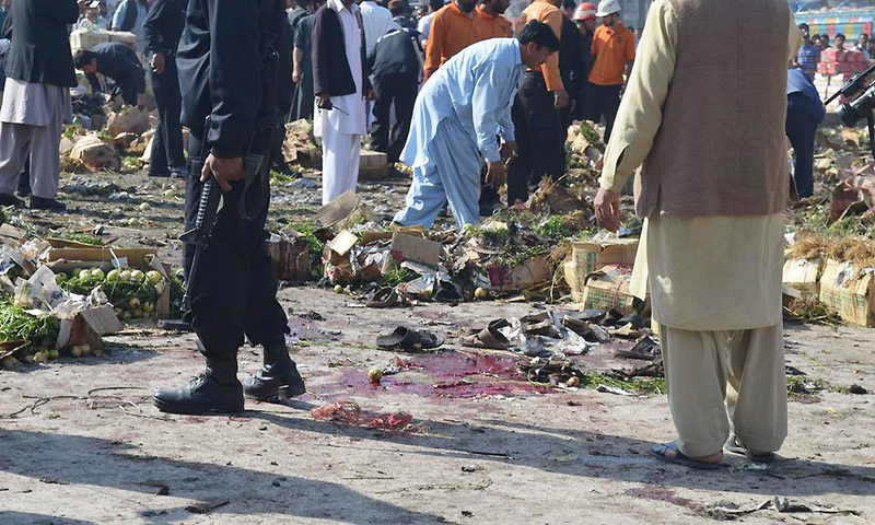 Locals and law enforcement gathered at the Sabzi Mandi blast site - Photo by Irfan Haider