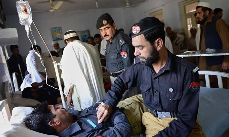 Pakistani policemen tend to their injured colleagues at a hospital following a bomb attack in Charsadda bazaar.—Photo by AFP