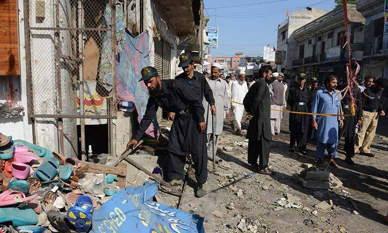 Pakistani police officials inspect the site of a bomb attack in Charsadda bazaar. —Photo by AFP