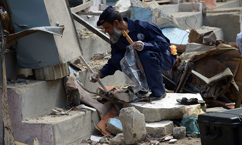 A security person collects evidence at the site of a bomb attack in Karachi on April 24, 2014. — Photo by AFP