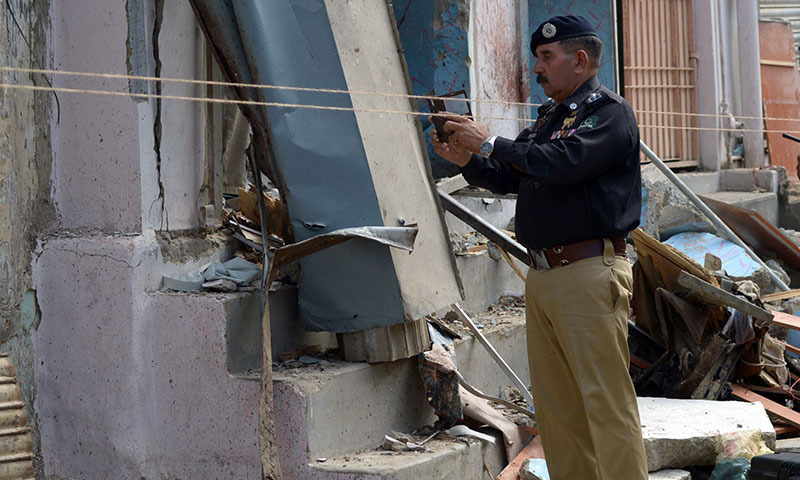 A police officer takes photographs of a bomb attack site in Karachi on April 24, 2014.— Photo by AFP