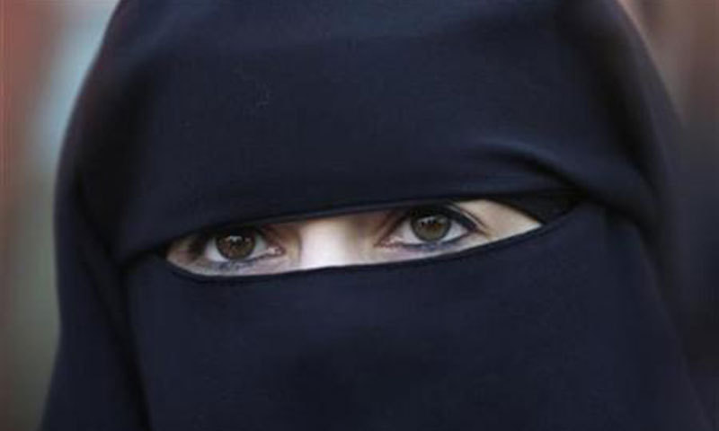 A young women wearing a black burqa which has a separate piece of cloth to  cover 360dd6d2a0