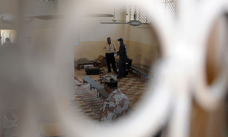 Forensic experts collect evidence at a  seminary after a bomb attack in Karachi on April 28, 2014. — Photo by AFP