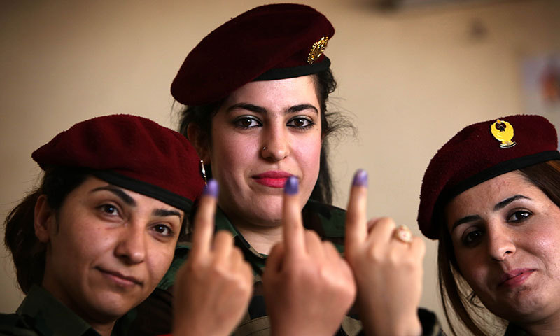 Members of the Kurdish Peshmerga force show their ink-stained fingers in the northern Kurdish city of Arbil on April 28, 2014. – AFP