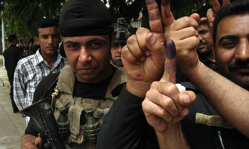 Members of the Iraqi security forces display their ink-stained fingers after casting their vote on April 28, 2014, outside a polling station in the city of Ramadi, west of the capital Baghdad. – AFP