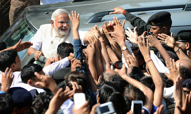 Narendra Modi greets supporters after casting his vote at a polling station in Ahmedabad on April 30, 2014. -Photo by AFP