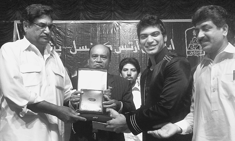 Former minister Aqil Shah awards a shield to Mohammad Shoaib during a reception at Nishtar Hall, Peshawar.—Dawn