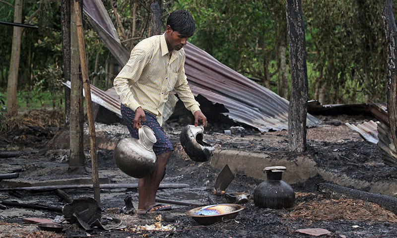 A villager salvages utensils from a burnt house after the area was set on fire in ethnic violence at Khagrabari village, in the northeastern Indian state of Assam, Saturday, May 3 2014. — Photo by AP