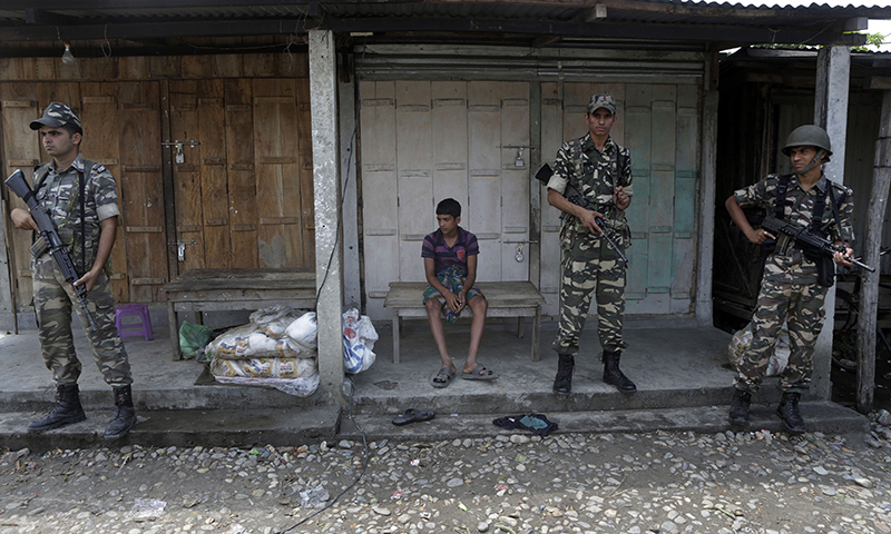 A villager sits on a bench as Indian security officers stand guard at violence-affected Narayanguri village, in the northeastern Indian state of Assam, Saturday, May 3 2014. — Photo by AP