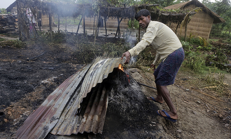 A villager removes sheets of tin from a fire after most homes were set on fire in ethnic violence at Khagrabari village, in the northeastern Indian state of Assam, Saturday, May 3 2014. — Photo by AP