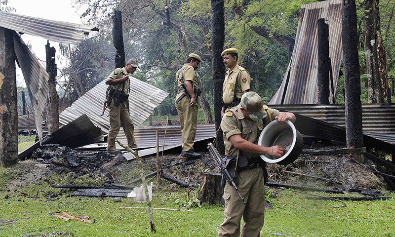 Indian security personnel inspect the debris of the houses that were burnt during attacks at Baksa district in the northeastern Indian state of Assam May 3, 2014. — Photo by Reuters