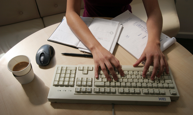 A generic picture of a woman working in an office sitting at her desk typing on a computer. — Reuters Photo