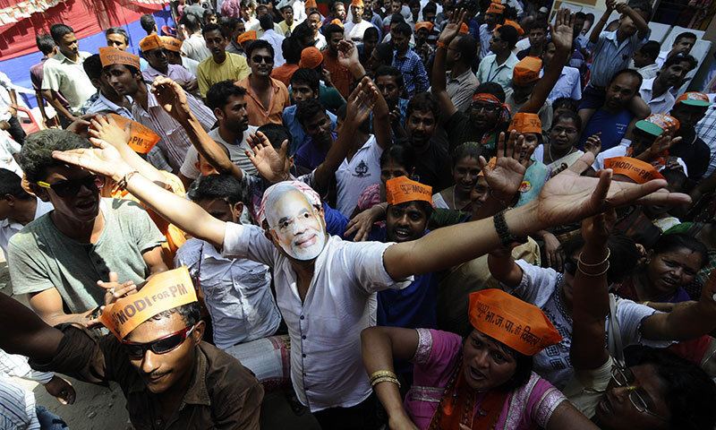 An Indian Bharatiya Janata Party (BJP) worker wears a mask bearing the image of BJP prime ministerial candidate Narendra Modi as he celebrates with others outside the party office in Guwahati. -AFP Photo