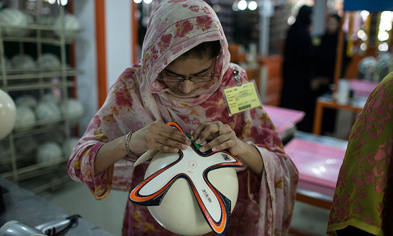 An employee adjusts outer panels of a football inside the football factory that produces official match balls for the 2014 World Cup in Brazil, in Sialkot. -Reuters Photo