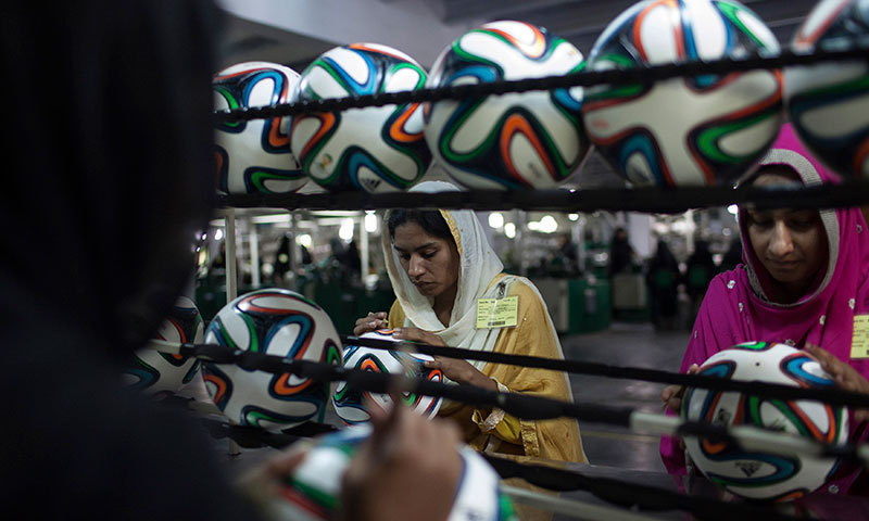 An employee conducts a final check to fix any cavity in the seams of a ball inside the football factory that produces official match balls for the 2014 World Cup in Brazil, in Sialkot. -Reuters Photo
