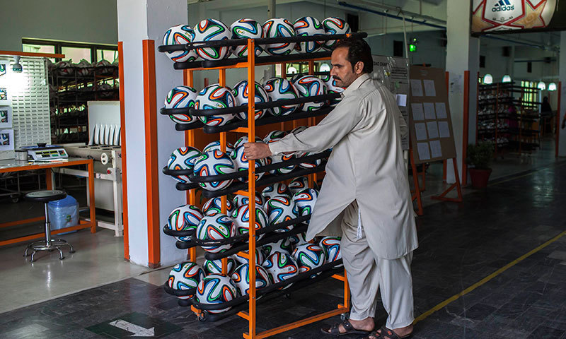 An employee takes finished balls out of the production area inside the football factory that produces official match balls for the 2014 World Cup in Brazil, in Sialkot. -Reuters Photo