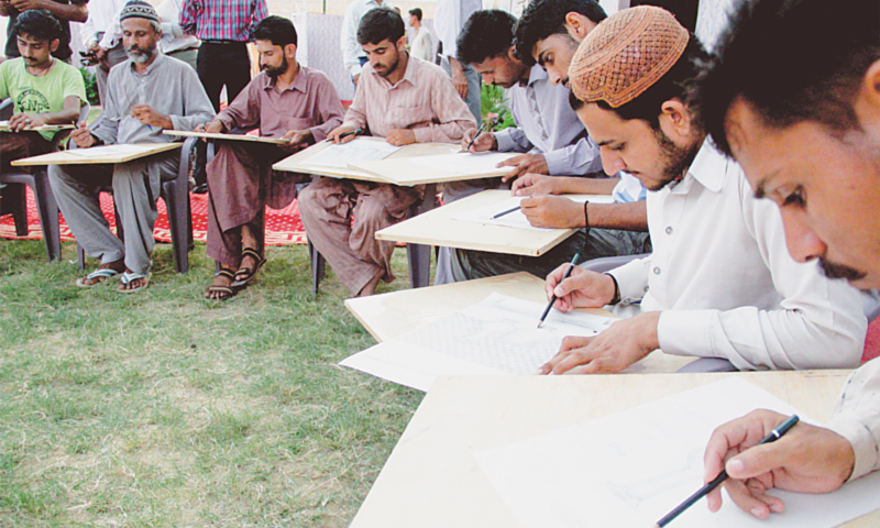 Inmates, all Fine Arts students at District Prison Malir, sit in a semicircle to sketch still lifes at the inauguration of the Sadequain School of Fine Arts, Computer Lab and English Language Centre on Sunday.—Hussain Afzal / White Star
