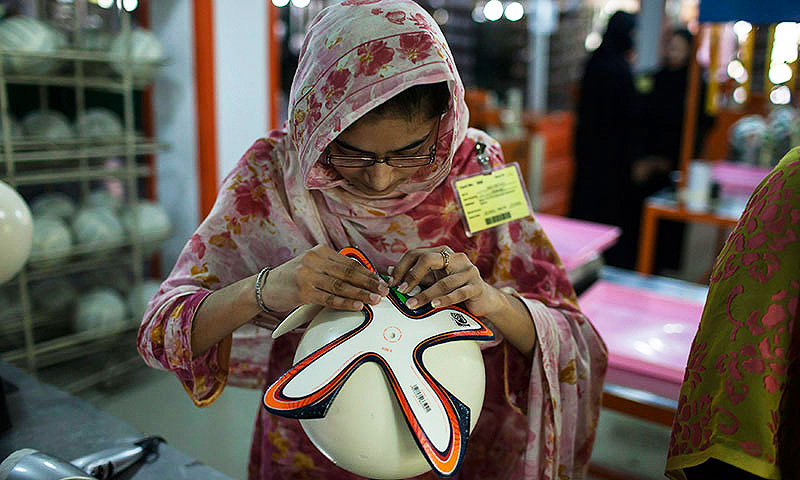 An employee adjusts outer panels of a football inside the factory that produces official match balls for the 2014 World Cup in Brazil, in Sialkot. -Reuters Photo