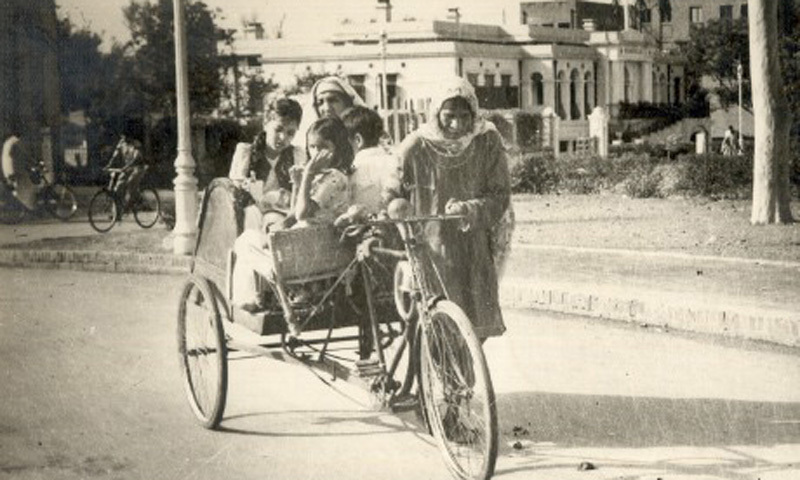 A woman pulls and carries passengers on a three-wheel-cycle in Lahore (1967).