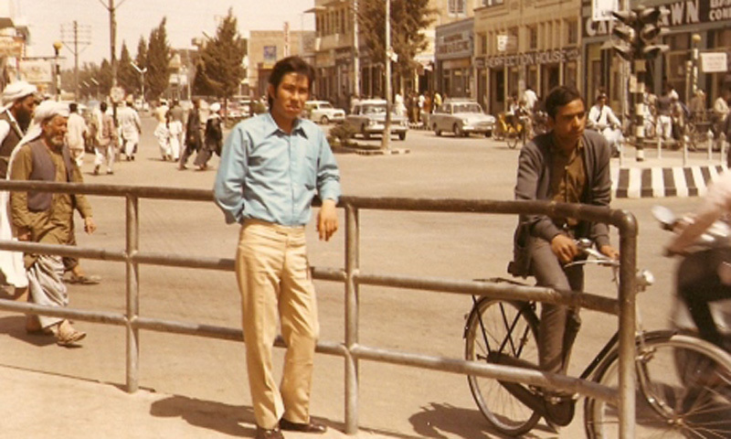 A college student poses in front of a street in Quetta (1972).