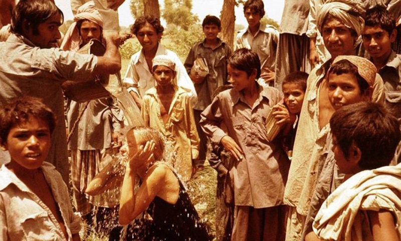 Natives of a Sindhi village drench a European tourist with cold water from a well to beat the summer heat (1975).