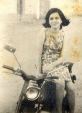 A young Pakistani Zoroastrian woman sitting on her motorbike in the Soldier Bazar area of Karachi (1969).