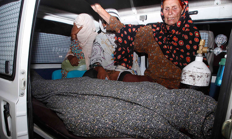 Women mourn over the body of Farzana Parveen in an ambulance outside of a morgue in Lahore. — Photo by Reuters