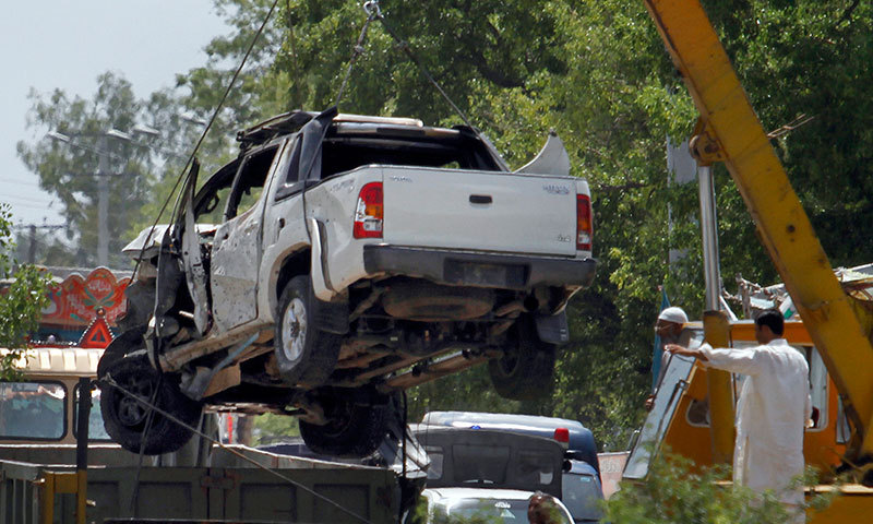 Damaged vehicle being removed from the site of a suicide bombing near Rawalpindi. —AP photo