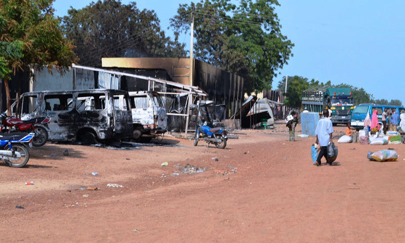 People walk past burnt vehicles and shops burnt by Boko Haram in Nigeria. — File photo