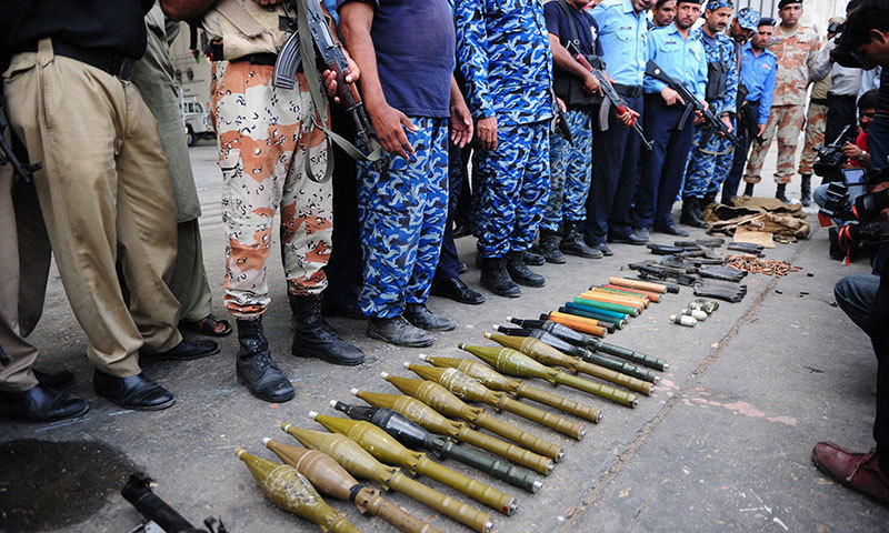 Policemen show seized weapons after militants attacked Jinnah International Airport in Karachi on June 9, 2014. — Photo by AFP