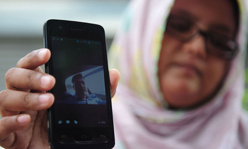 A woman holds up a cellphone displaying an image of a missing relative following an assault by militants at Karachi airport in Karachi on June 9, 2014. – AFP Photo