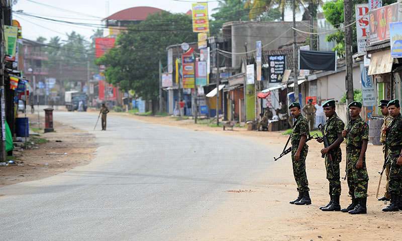 Sri Lankan Special Task Force (STF) soldiers stand guard at the roadside after clashes between Muslims and an extremist Buddhist group in the town of Alutgama on June 16, 2014. — Photo by AFP