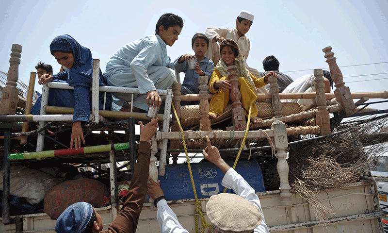 Pakistani civilians, fleeing from a military operation in North Waziristan tribal agency, arrive in Bannu district on June 18, 2014. — Photo by AFP