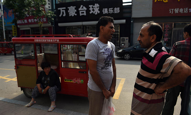 Refugee Waheed (C) and asylum seeker Hameed (R) waiting for a bus in Sanhe, in China's Hebei province, east of Beijing. Photo by AFP