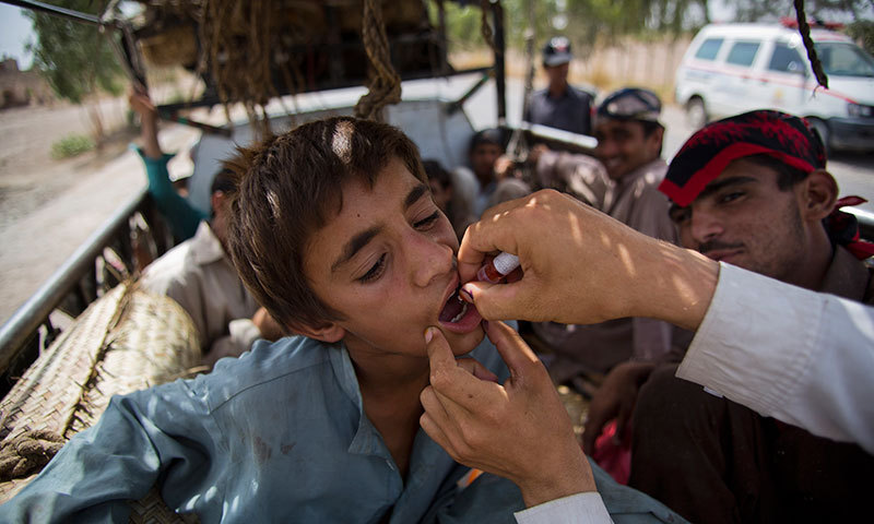 In this photo taken on Friday, June 27, 2014, a volunteer gives polio vaccine to a displaced tribal boy in Bannu, Pakistan.—AP photo