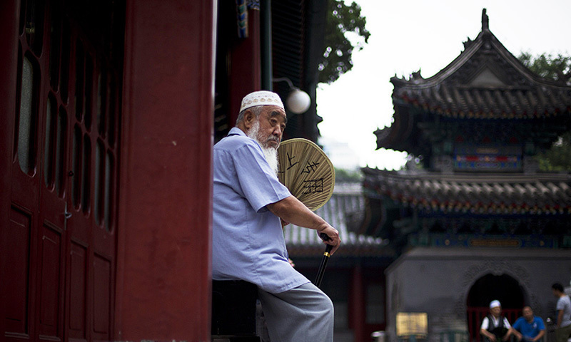 A Chinese Muslim man fans himself as he waits for the time to break his fast. -Photo by AP