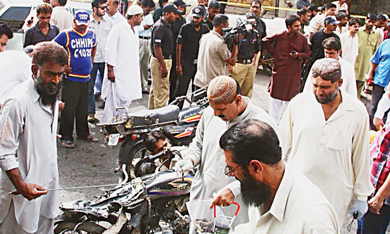 Officials collect evidence from the motorcycle blast site in Saddar on New Preedy Street on Friday.—Online