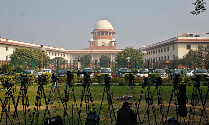 A television journalist sets his camera inside the premises of the Supreme Court in New Delhi. — File photo