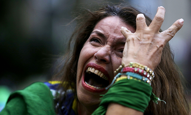 A Brazilian fan cries as she watches her team during a live telecast of the semifinals. -Photo by AP